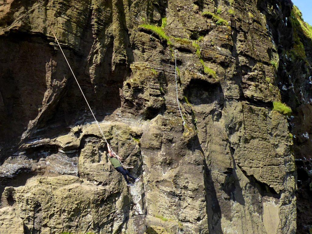 Männer üben Sprangan an den Felsen, Westmänner Inseln