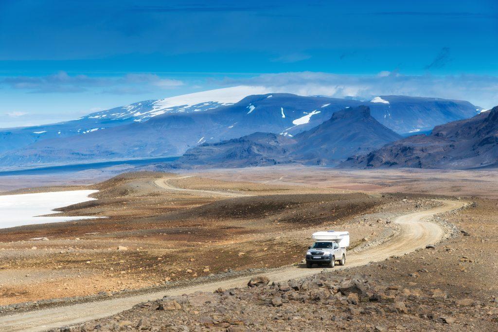 Ein Camper fährt über eine Schotterpiste im Hochland, Gletscher im Hintergrund
