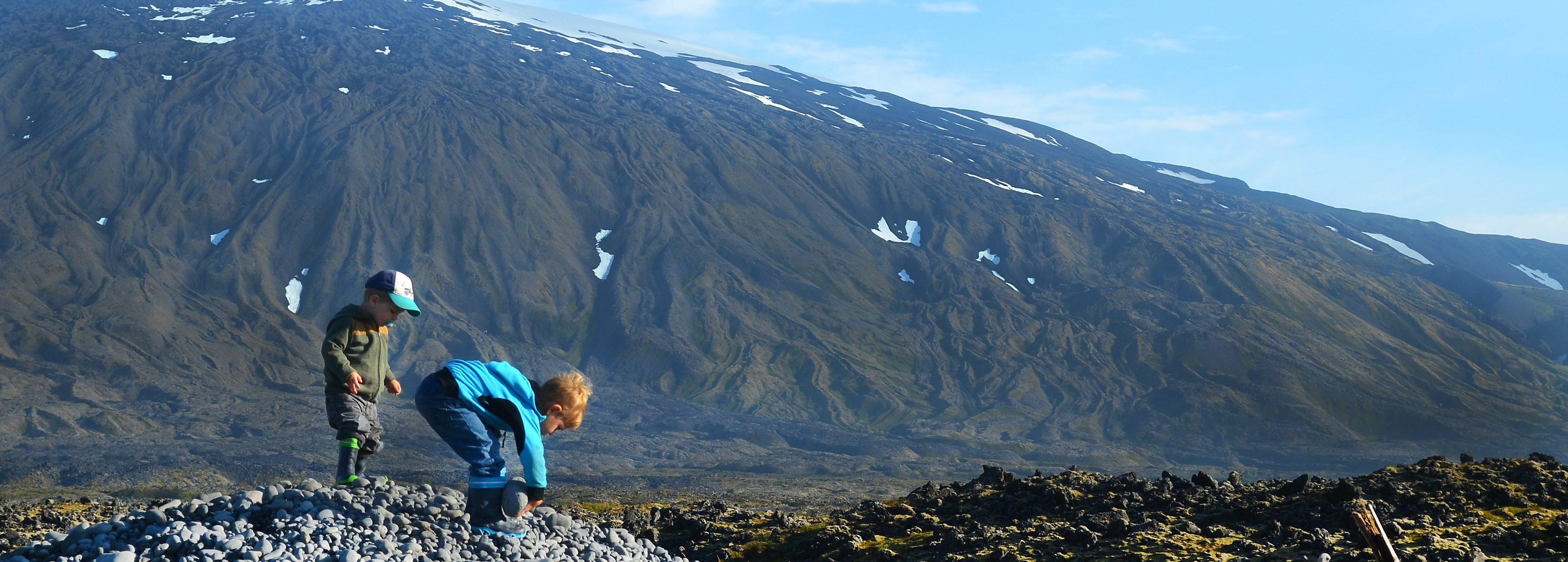 Kinder spielen auf einem Steinhaufen vor den Füßen des Gletschers Snaefellsjökull in West- Island