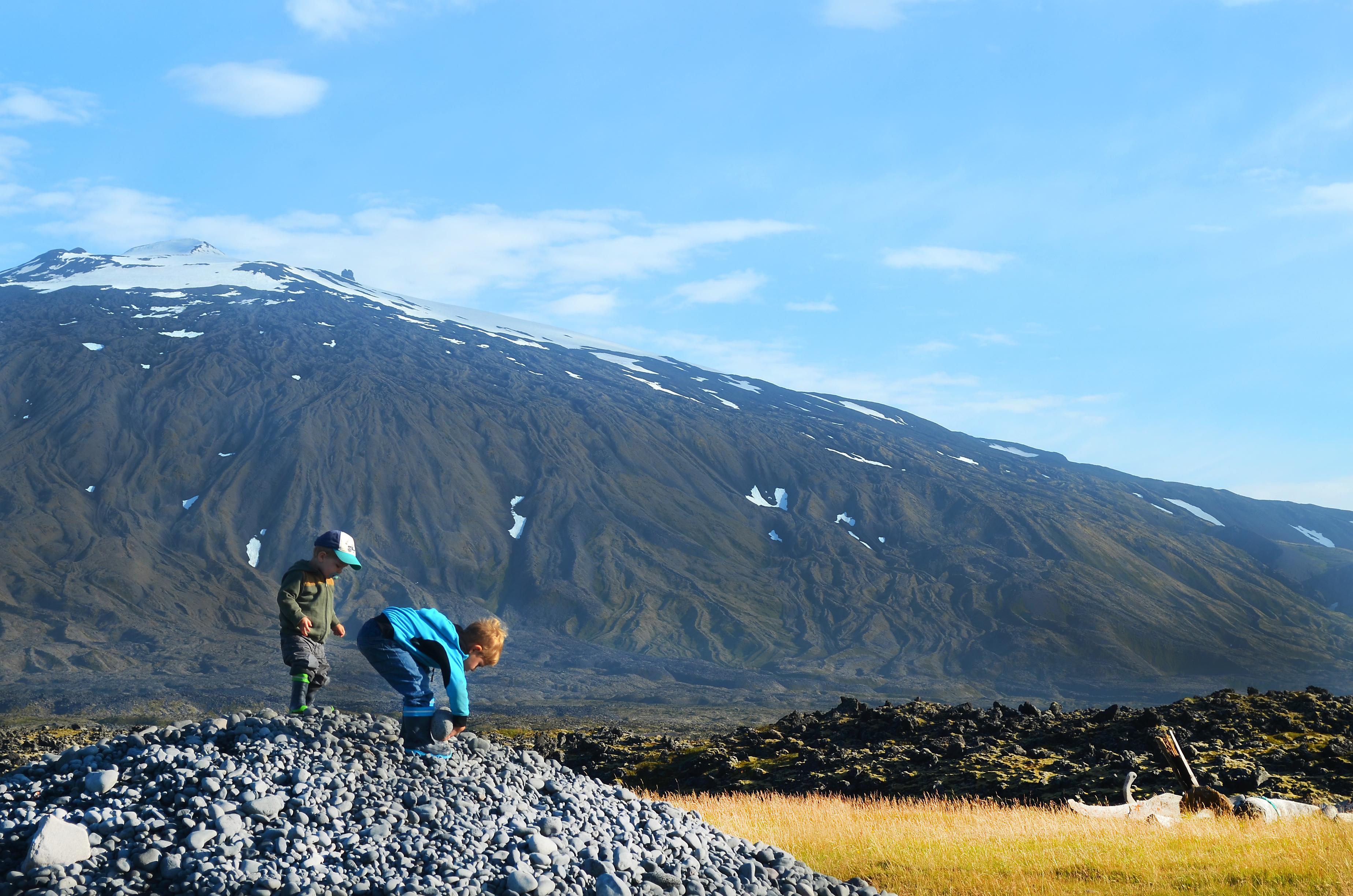 Kinder spielen auf einem Steinhaufen vor den Füßen des Gletscher Snaefellsjökull