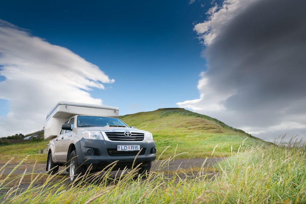 Camper in Islands Landschaft, Blauer Himmel