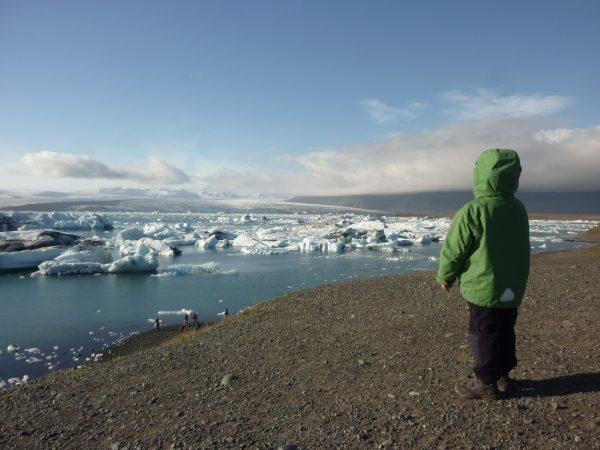 Kind steht an der Gletscherlagune, Südostisland
