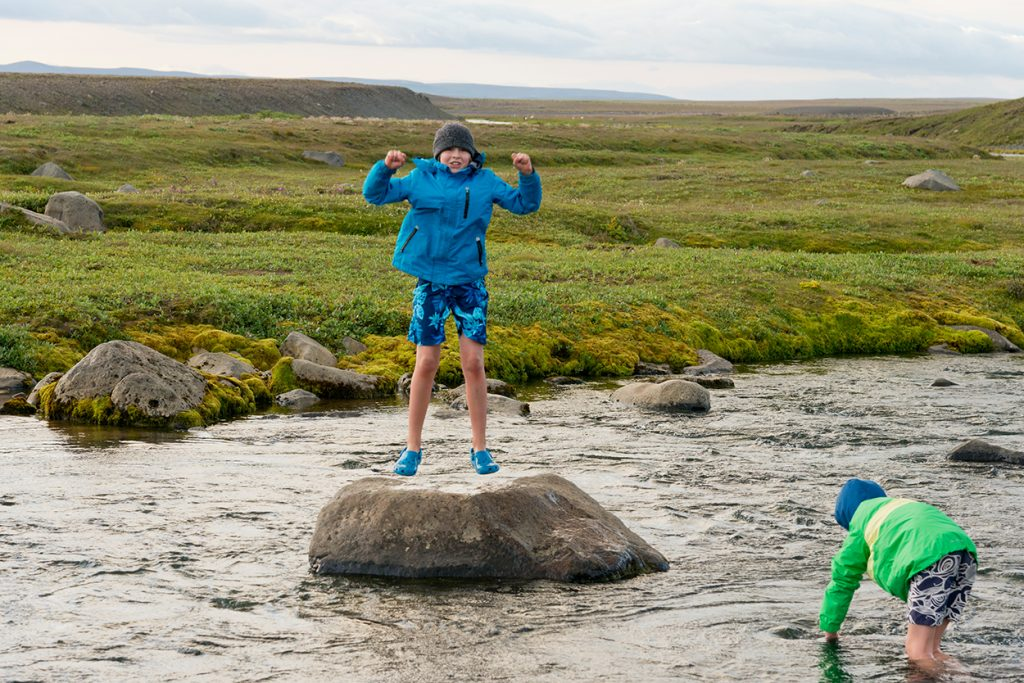 Kind auf Felsblock im Fluss in Island