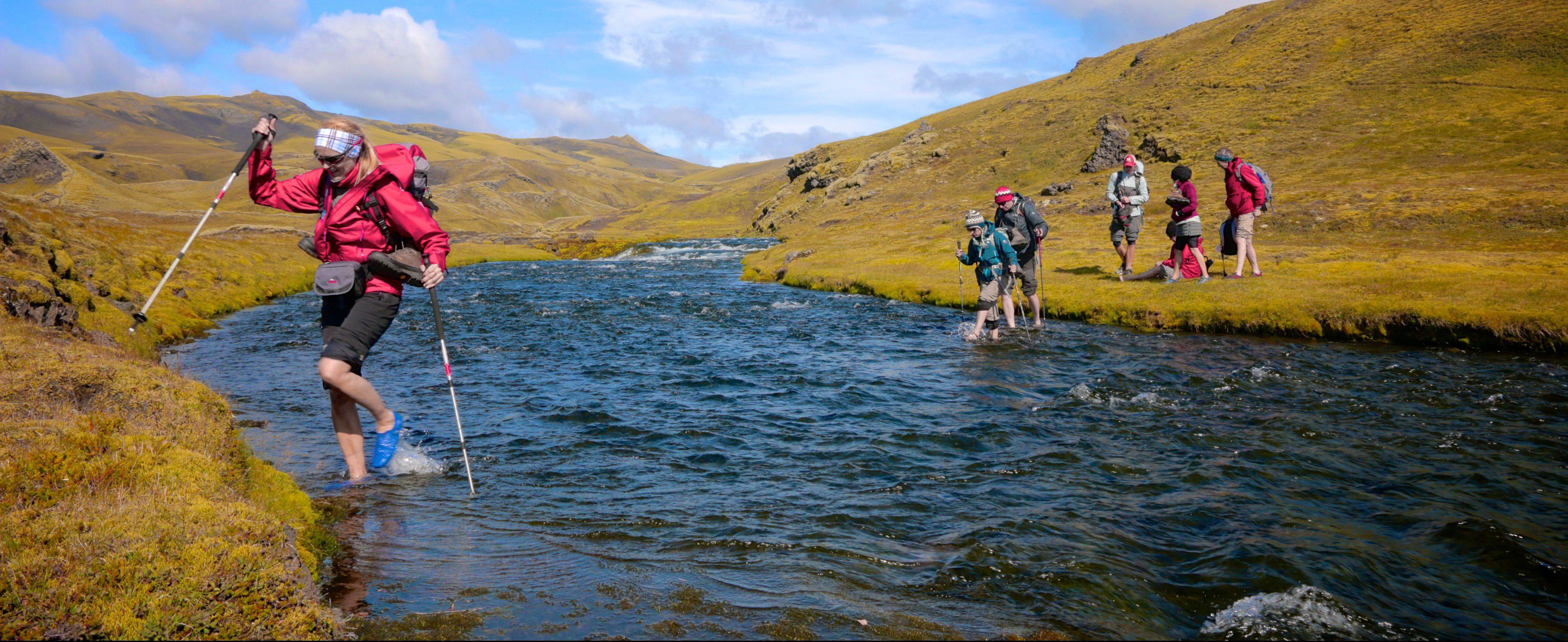 Wanderer überqueren einen Bach im Hochland von Island
