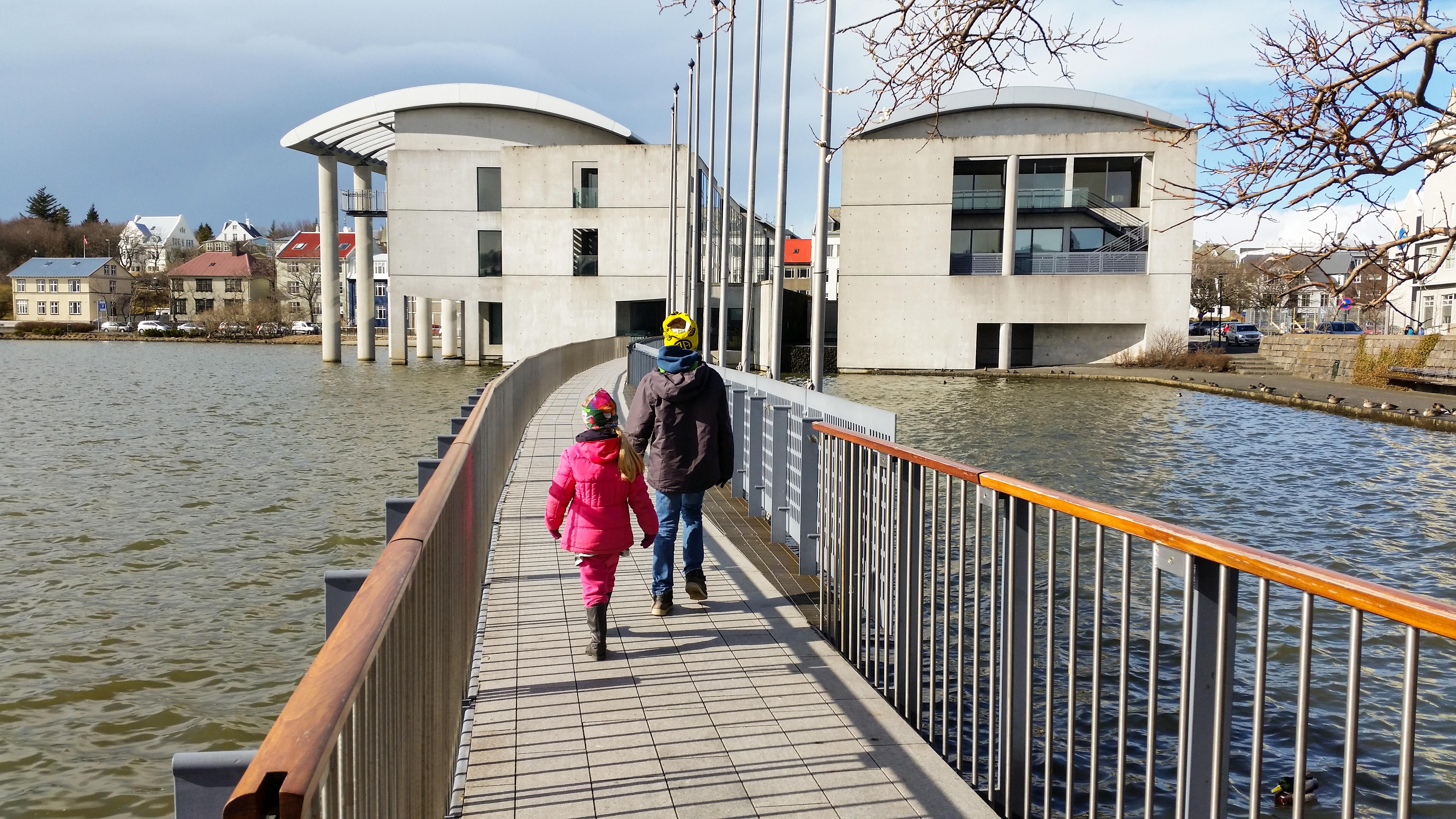 Kinder laufen über eine Brücke des Tjörnin Stadtteiches zum Rathaus