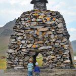 Kinder bestaunen einen Denkmal auf Snaefellsnes