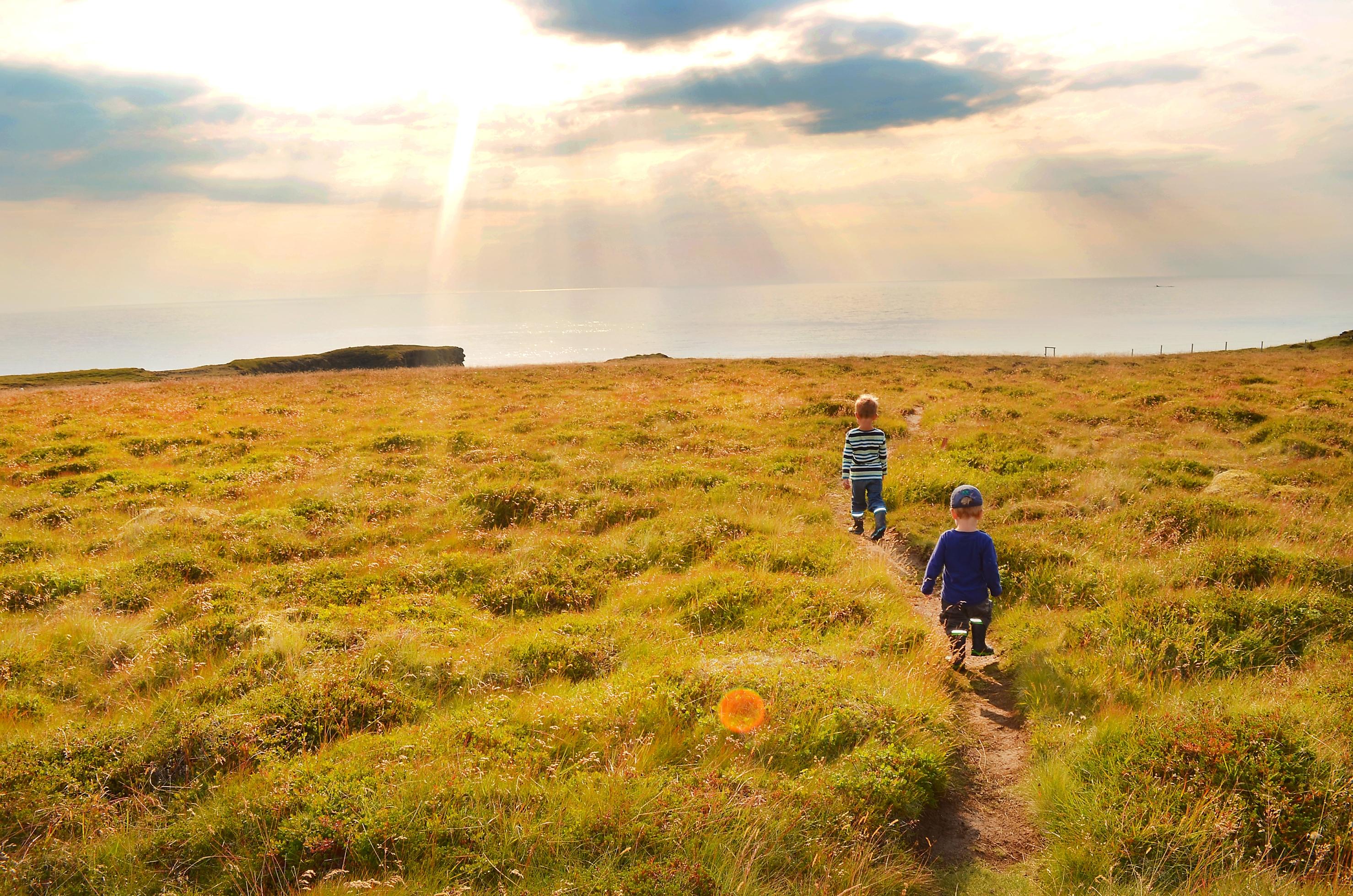 Kinder laufen über einen Pfad an der Küste von Snaefellsnes