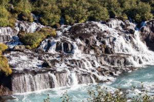 Wasser kommt aus dem Boden und stürzt in einen Bach, Lavawasserfälle