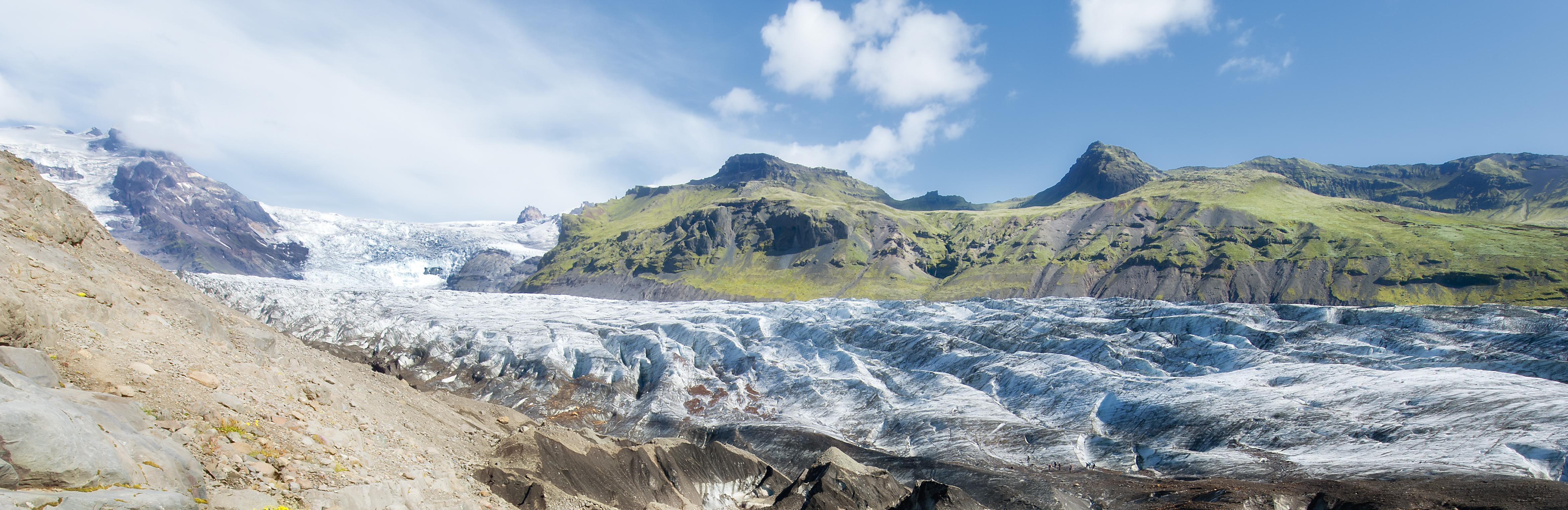 Gletscher mit grünen Bergen im Hintergrund