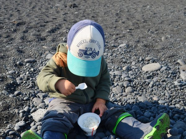 Kind macht Picknick am Steinstrand