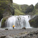 Kirkjubæjarklaustur, Wasserfall, Man mit gelber Jacke