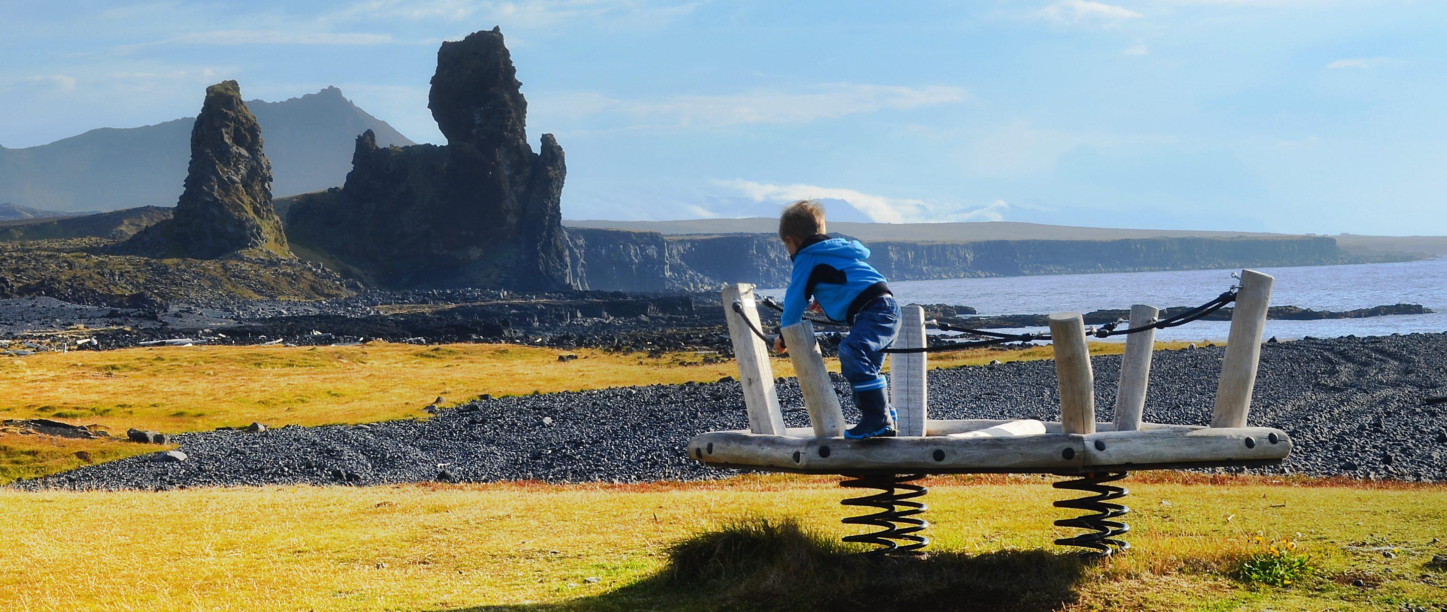 Kind auf einem Spielplatz am Meer mit Felsenküste in Island