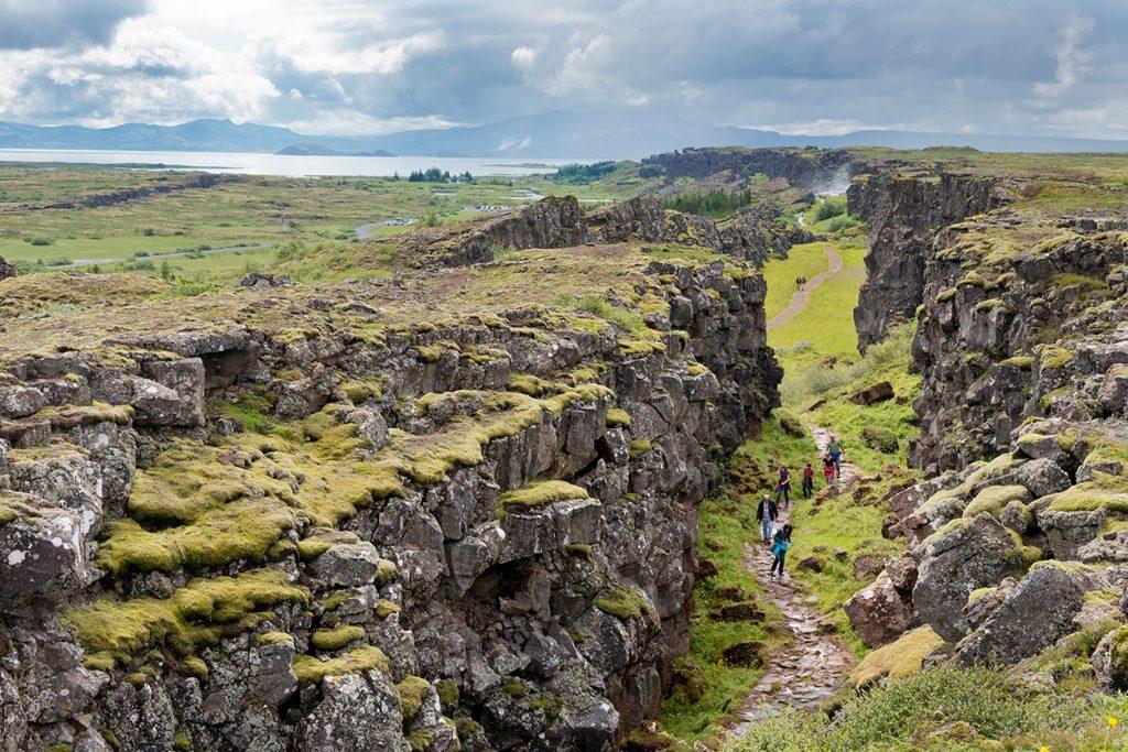 Wanderer in Erdspalte in Island mit Blick auf Landschaft