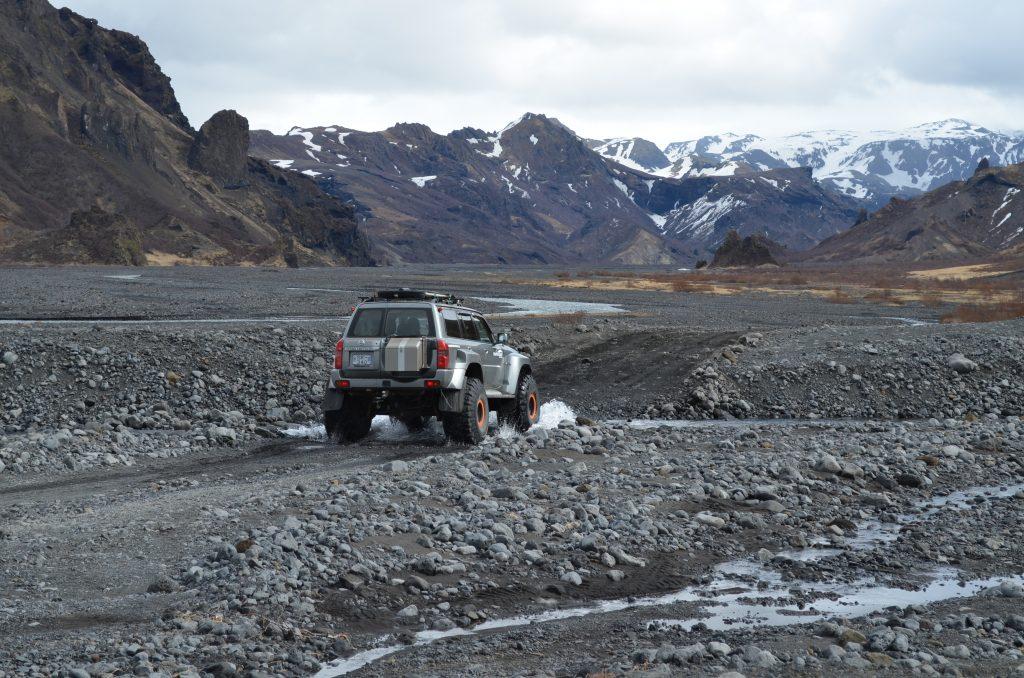 Ein jeep fährt durch eine kleine Furt im Hochland von Island, Thorsmörk