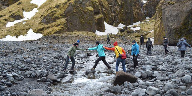 Mitglieder des Teams von Katla Travel helfen sich gegenseitig über einen Bach in Island