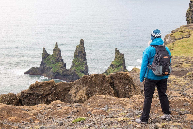 Wanderin genießt die Aussicht auf die Troll-Felsen im Meer in Südisland nahe Vík
