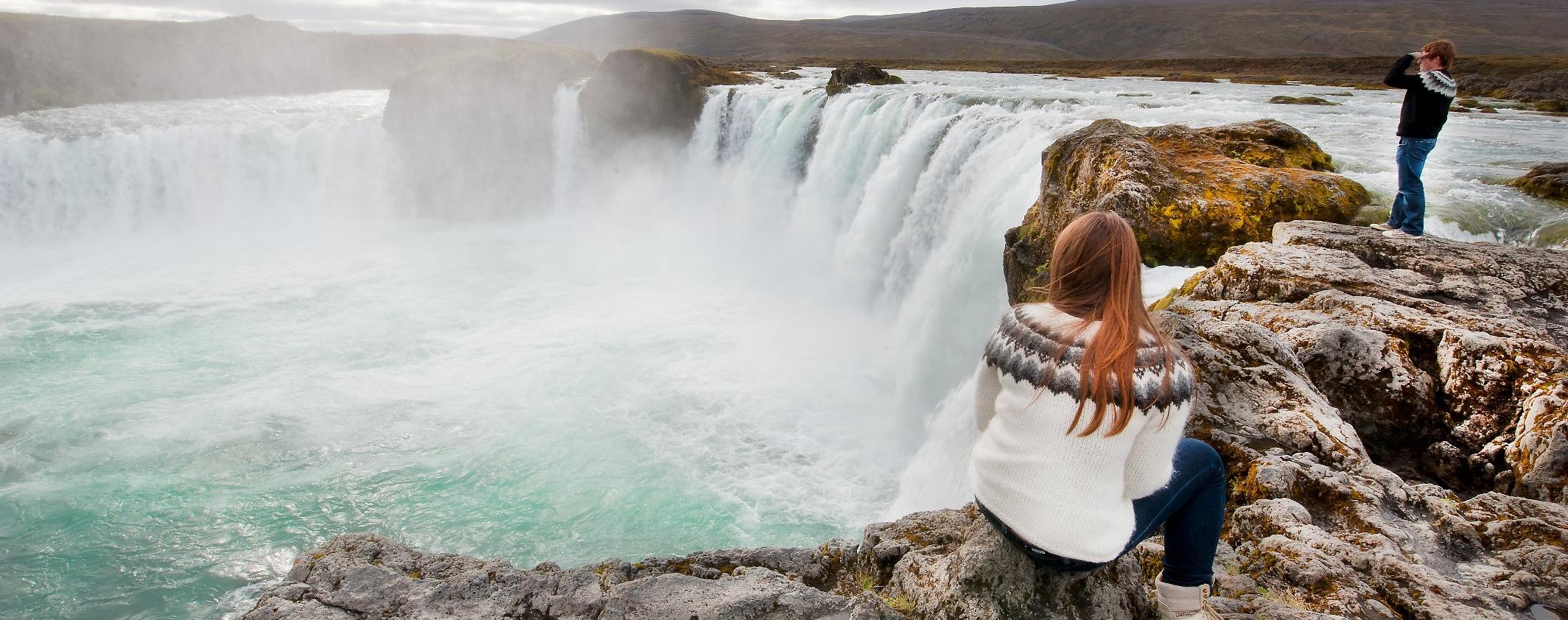 Frau mit Islandpulli beobachtet den Wasserfall Godafoss