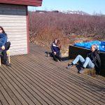 Journalisten sonnen sich auf der Terasse eines Ferienhauses in Island