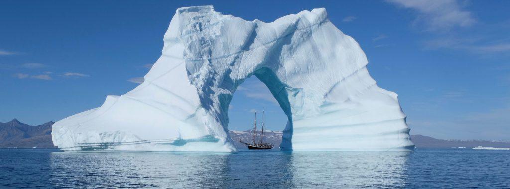 gigantischer Eisberg mit Loch in der Mitte - man sieht ein Segelschiff vorbeifahren