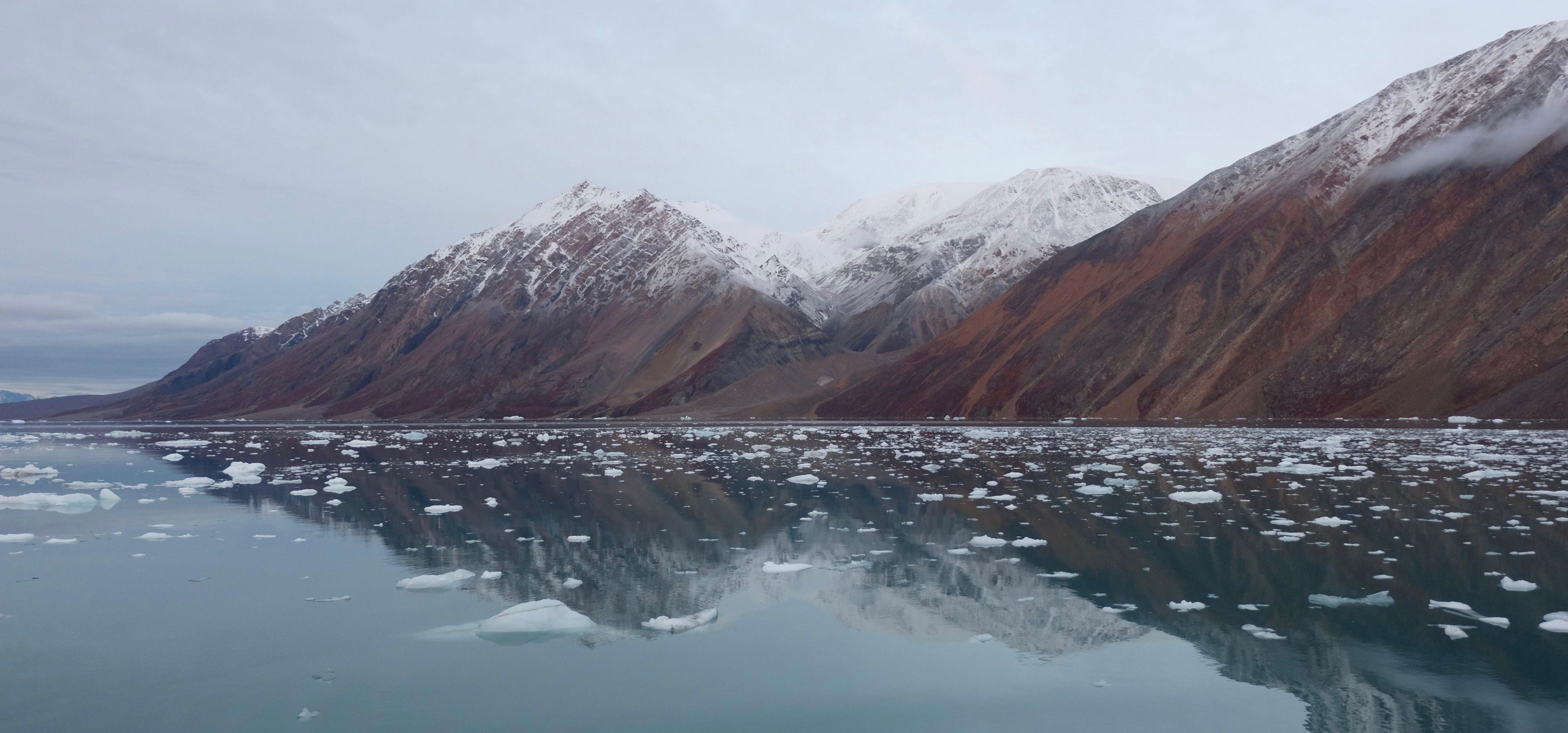 Berge spiegeln sich im Eiswasser im Scoresbysund in Grönland