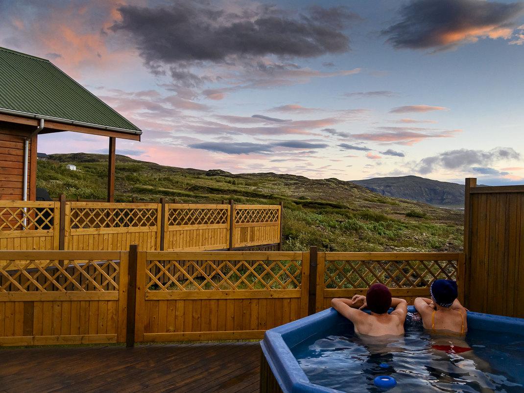 Zwei Urlauber im Hot Pot des Ferienhauses Oskasteinn