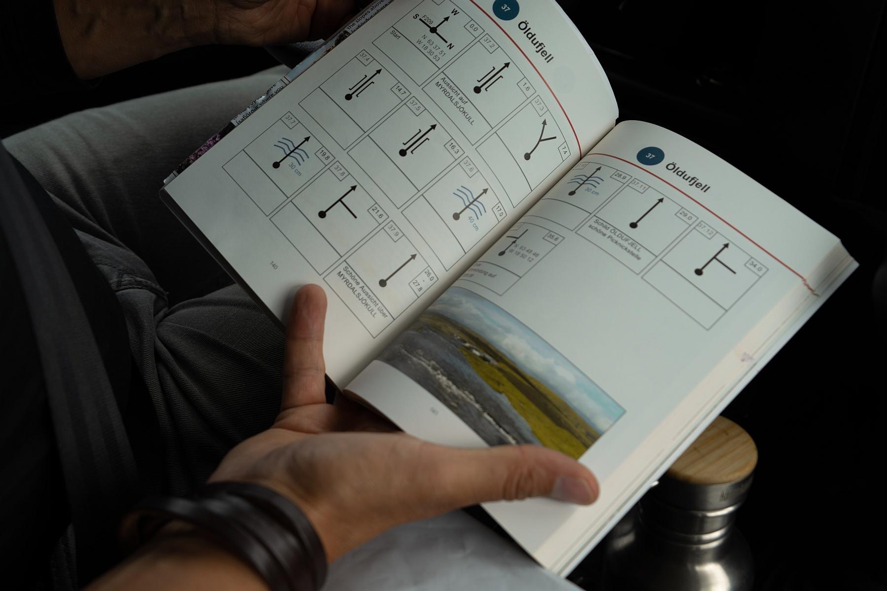 Reisender schaut in das Trackbook für Fahrt durch Island