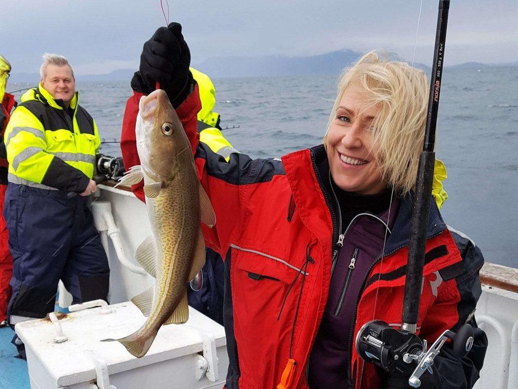 Frau hält gefangenen Fisch auf Boot vor Islands Küste