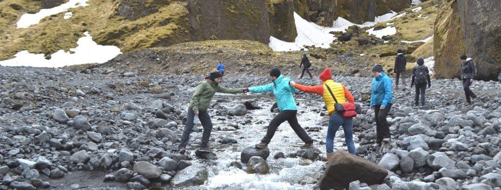 Katla Team Mitarbeiter helfen sich beim überqueren eines Baches