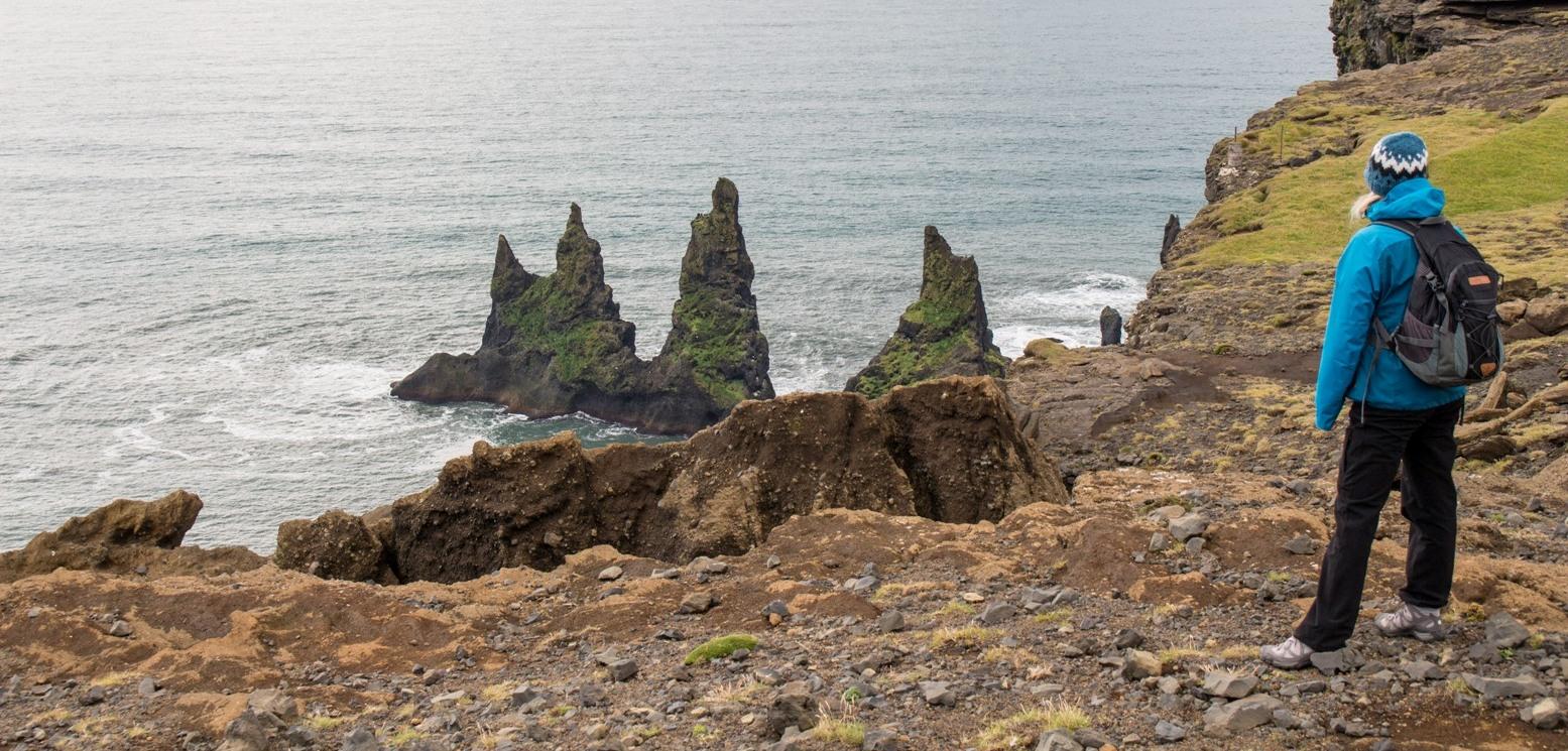 Wilde Küstenlandschaft mit Felsen im Meer, Reisende schaut auf das Meer