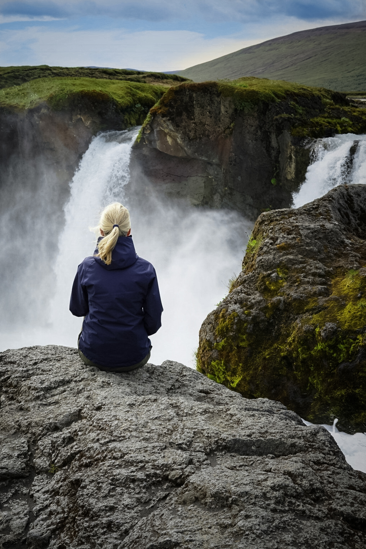 Frau sitzt am Wasserfall Godafoss in Nordisland