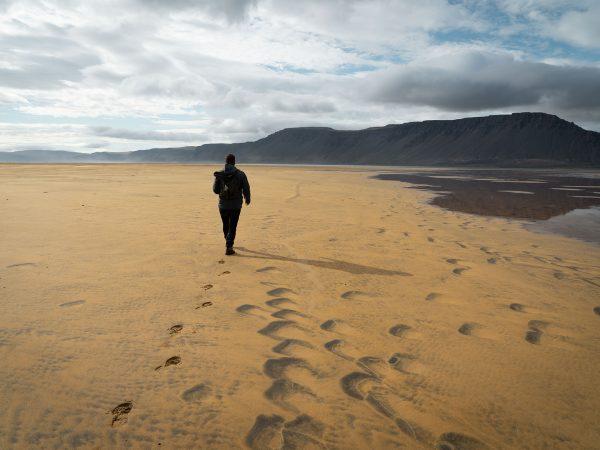 Spaziergänger am Strand von Raudisandur in den Westfjorden, Island
