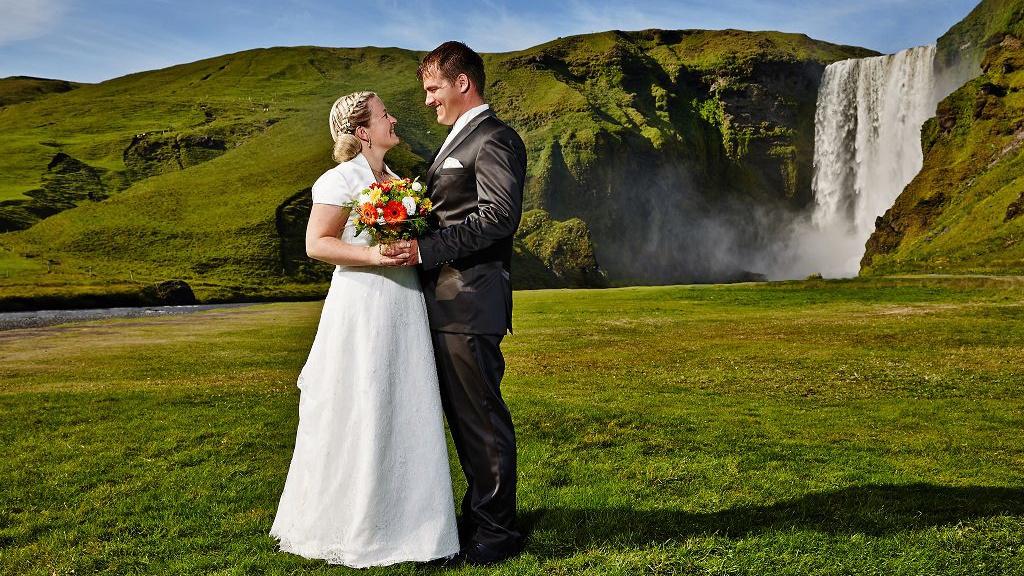 Hochzeitspaar auf grüner Wiese vor einem Wasserfall in Island