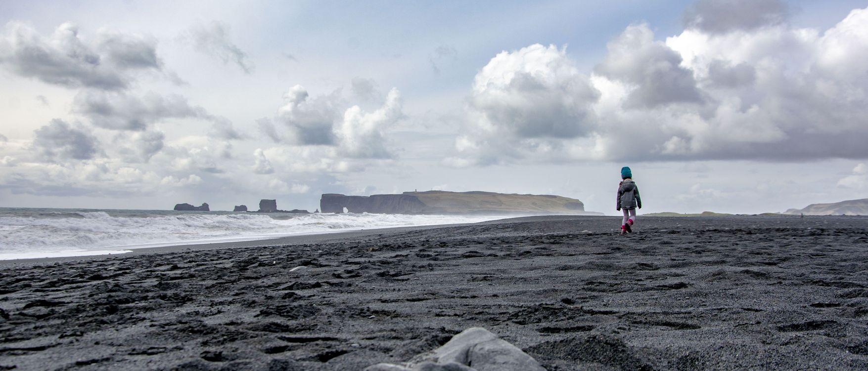 Kind läuft am Strand von Vik durch den Sand