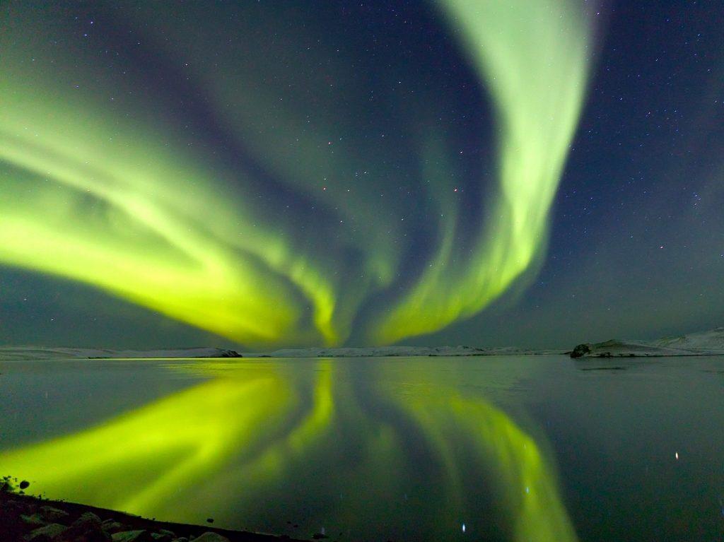 grüne Nordlichter spiegeln sich in einem See in Island
