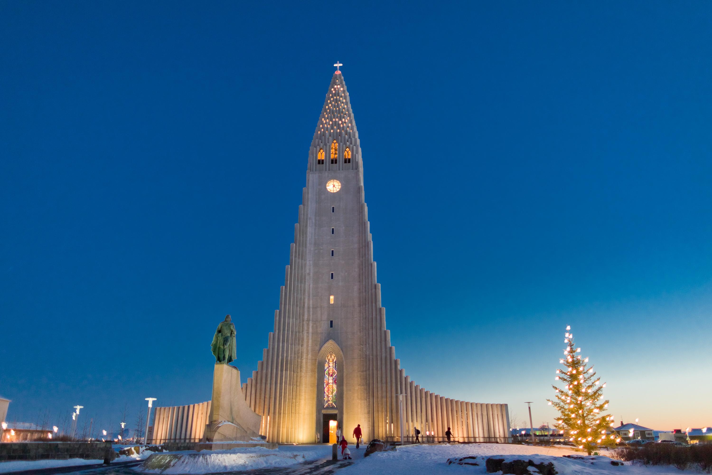 Hallgrimskirche in Reykjavik umgeben von weihnachtlichen Lichtern und Schnee