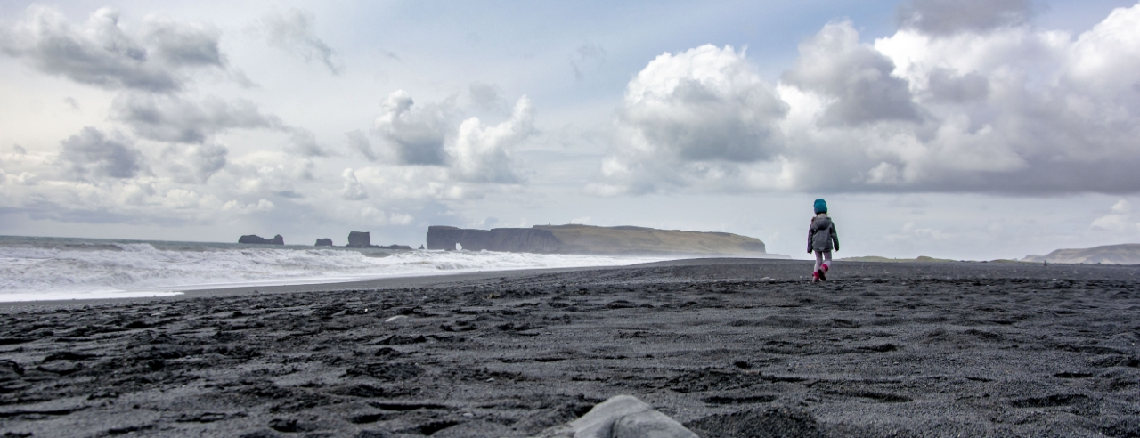 Kind läuft am Strand von Vík - sicher reisen in Island
