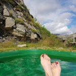 Füße schauen aus einem Hot Pot heraus in Südostisland