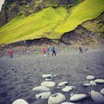 Wanderer am Strand bei Südisland, Moosbewachsene Felsen im Hintergrund