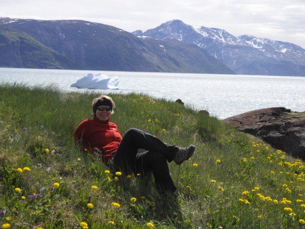 Frau entspannt auf einer grünen Wiese mit Blick auf den Eisfjörd und die Eisberge