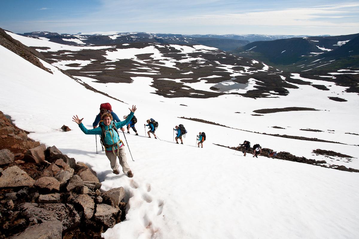 Wandergruppe läuft über ein Schneefeld in Island