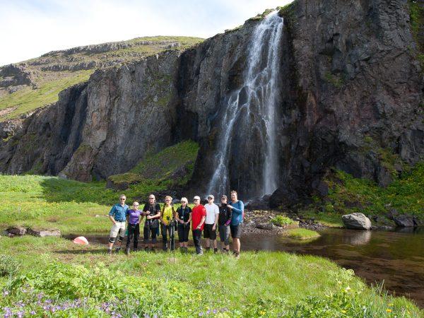 Wandergruppe posiert vor einem Wasserfall in Island