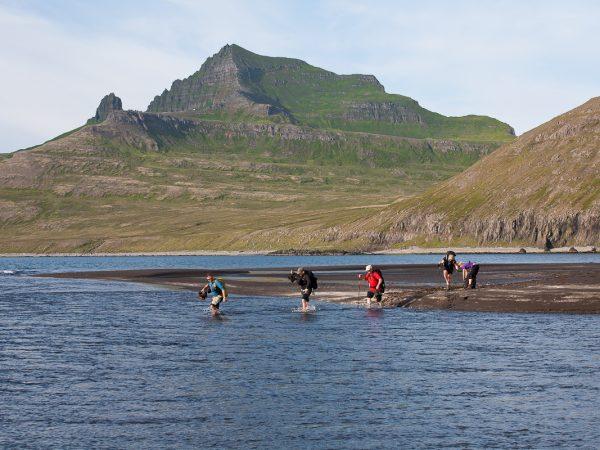 Wandergruppe in Island läuft barfuß durch einen breiten Bach