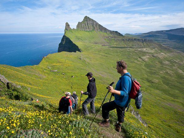 Wanderer beim Aufstieg in den Westfjorden, Hornbjarg, ein markanter Berg im Hintergrund