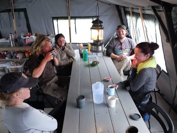 Menschen genießen gemeinsam einen Snack im Zelt