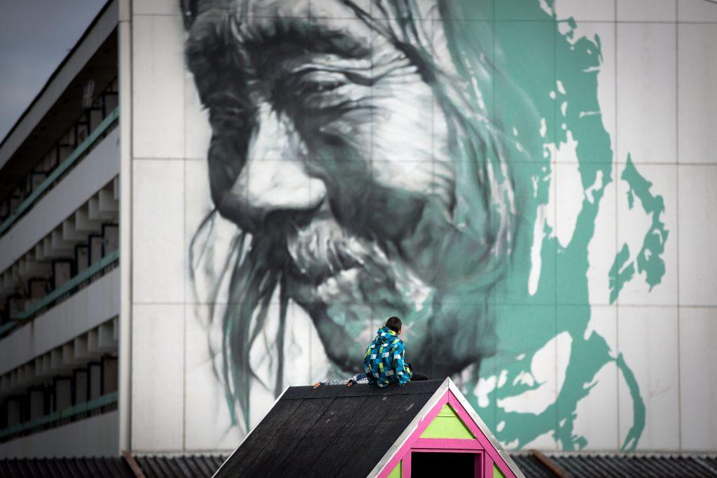 Junge schaut auf Guido van Helten Gemälde in Nuuk, Grönland